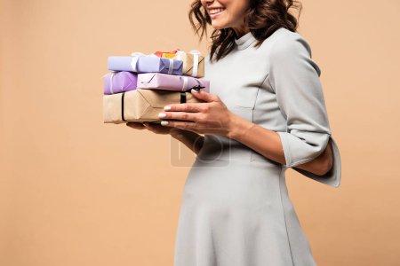 Photo pour Vue recadrée de la femme enceinte en robe grise tenant des cadeaux sur fond beige - image libre de droit