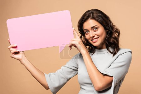 Photo for Smiling woman in grey dress holding speech bubble on beige background - Royalty Free Image