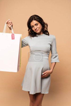 Photo pour Femme enceinte en robe grise tenant des sacs à provisions sur fond beige - image libre de droit