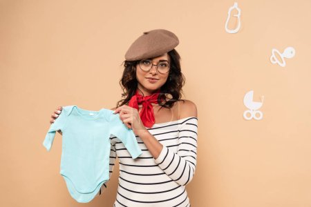 Photo pour Pregnant french woman in beret holding overalls isolated on beige - image libre de droit