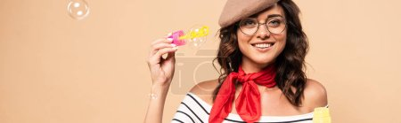 panoramic shot of french woman in beret holding bottle with soap bubbles on beige background