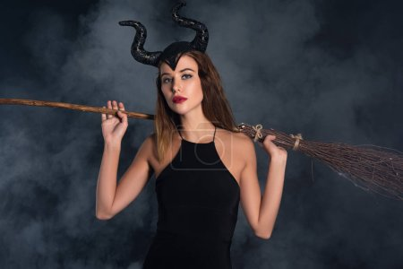 young woman with horns holding broom on black with smoke