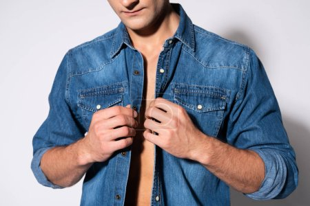 vista recortada del hombre tocando camisa de mezclilla en blanco