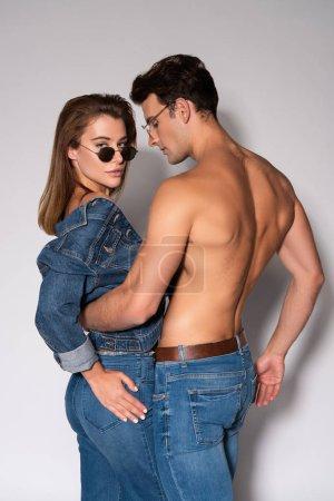 Photo pour Homme élégant en lunettes de soleil câlin fille en jean veste sur blanc - image libre de droit