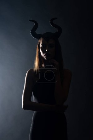 silhouette of young woman with horns standing on black