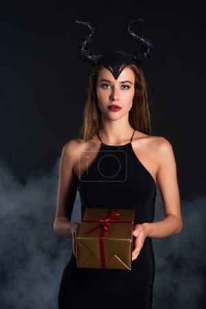 Photo pour Jolie femme avec des cornes tenant présent sur noir avec de la fumée - image libre de droit