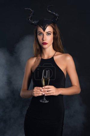 Photo pour Attrayant femme avec des cornes tenant verre de champagne sur noir avec de la fumée - image libre de droit