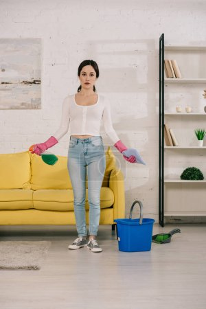 Photo pour Young, attractive housewife holding rag and spray bottle while standing near yellow sofa near bucket, brush and scoop on floor - image libre de droit