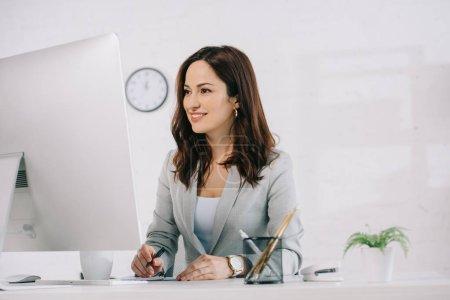 Photo pour Attrayant, secrétaire souriant regardant l'écran d'ordinateur et l'écriture dans le cahier - image libre de droit