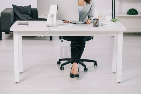 Photo pour Patial view of secretary in high heeled shoes sitting at workplace in office chair - image libre de droit