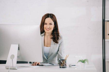Photo pour Attrayant, secrétaire souriant regardant la caméra tout en étant assis sur le lieu de travail - image libre de droit