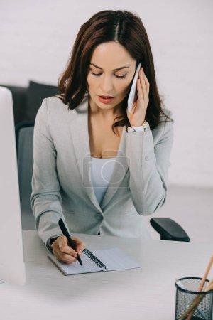 Photo pour Secrétaire attentive parlant sur un téléphone intelligent et écrivant dans un cahier pendant qu'elle est assise au travail - image libre de droit