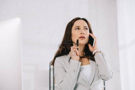 Photo pour Jeune, réfléchi secrétaire détourner les yeux tout en parlant sur smartphone dans le bureau - image libre de droit