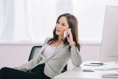 Photo pour Élégante et réfléchie secrétaire regardant dehors en parlant au téléphone intelligent au bureau - image libre de droit