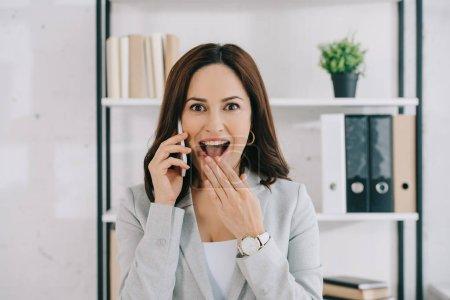 Photo pour Excité, secrétaire choqué en regardant la caméra tout en parlant sur smartphone - image libre de droit