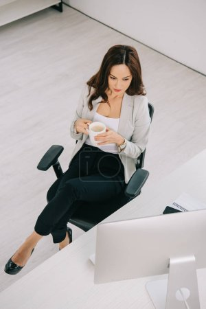 high angle view of young, elegant secretary sitting near workplace and holding coffee cup