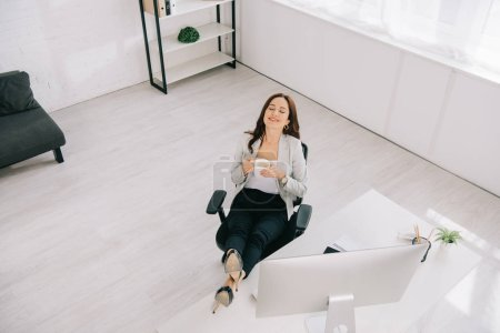 Photo pour High angle view of elegant, smiling secretary sitting near workplace with closed eyes and holding coffee cup - image libre de droit