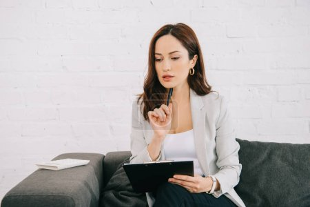 thoughtful young secretary holding clipboard and pen while sitting on couch in office