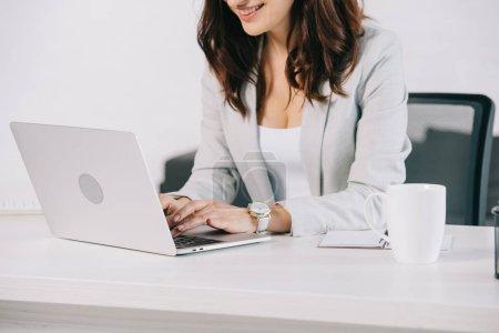 Photo pour Vue partielle du secrétaire souriant qui utilise un ordinateur portable alors qu'il est assis au bureau - image libre de droit