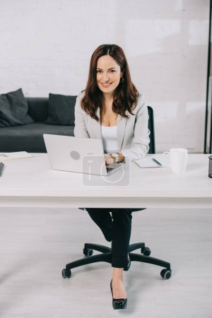 cheerful young secretary looking at camera while sitting at workplace in office
