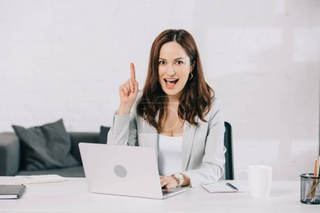 excited young secretary showing idea sign while sitting at workplace in office