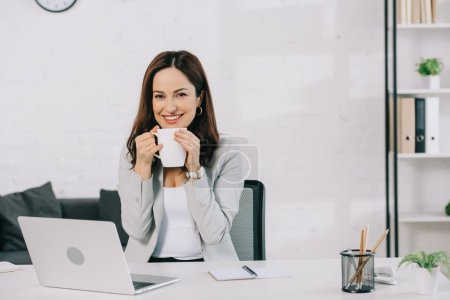 Photo pour Happy young secretary holding coffee cup and looking at camera while sitting at workplace in office - image libre de droit