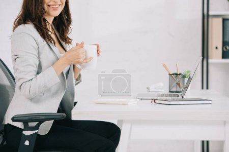 Photo pour Vue recadrée du secrétaire souriant tenant une tasse de café alors qu'il était assis au bureau - image libre de droit