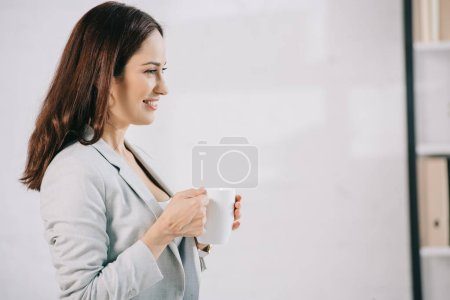 Photo for Smiling, young secretary looking away while holding coffee cup - Royalty Free Image