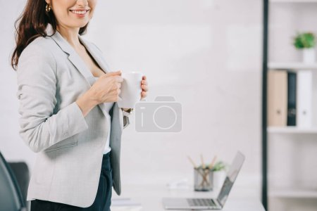 Photo for Cropped view of elegant secretary holding coffee cup in office - Royalty Free Image