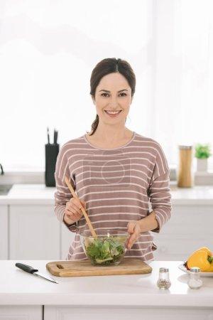 glückliche junge Frau blickt in die Kamera, während sie frischen Gemüsesalat mixt