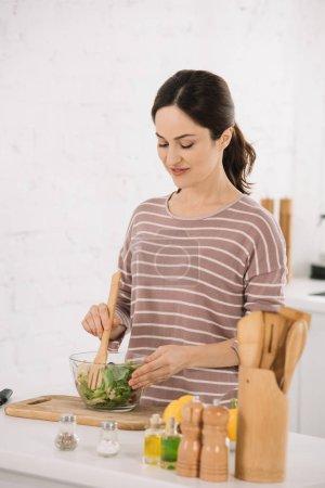 schöne junge Frau mixt frischen Gemüsesalat, während sie am Küchentisch steht