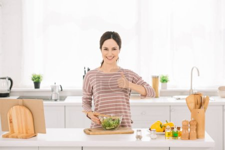 Photo for Happy young woman showing thumb up while standing near bowl with fresh vegetable salad - Royalty Free Image