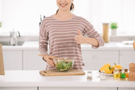 Photo for Cropped view of smiling woman showing thumb up while standing near bowl with fresh vegetable salad - Royalty Free Image