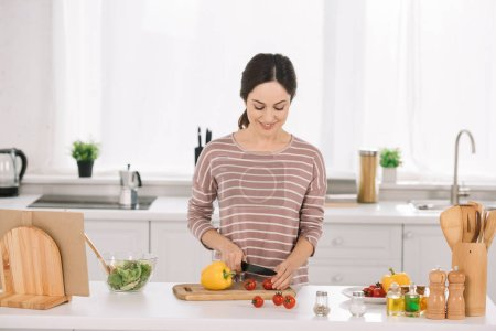 Photo pour Attractive, smiling woman cutting fresh vegetables on chopping board - image libre de droit