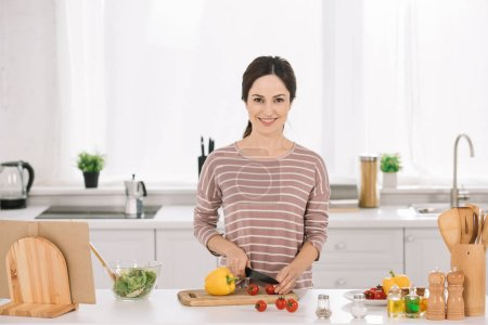 Photo for Young, happy woman cutting fresh vegetables on chopping board and looking at camera - Royalty Free Image