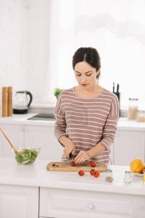 Photo pour Jeune femme séduisante coupant des légumes frais en planche à découper - image libre de droit