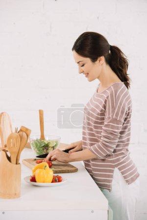 junge, lächelnde Frau schneidet frisches Gemüse auf Schneidebrett