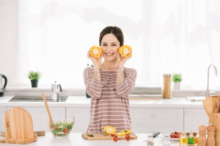 Photo for Attractive young woman looking at camera while standing near kitchen table with fresh vegetables and holding cut bell pepper - Royalty Free Image
