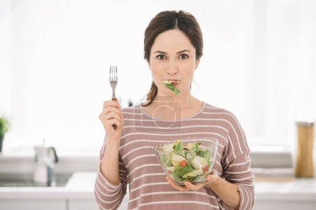 Photo for Attractive young woman looking at camera while holding fork and eating fresh vegetable salad - Royalty Free Image