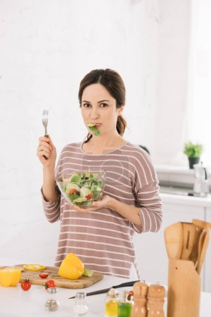 Photo for Beautiful young woman looking at camera while holding fork and eating fresh vegetable salad - Royalty Free Image