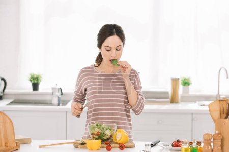 Photo for Pretty, young woman tasting salad while standing at kitchen table with fresh vegetables - Royalty Free Image