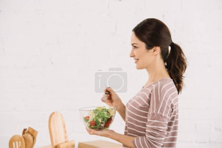 Photo for Side view of attractive, smiling woman holding bowl with fresh vegetable salad - Royalty Free Image