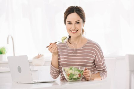 Photo for Young, happy woman looking at camera while sitting at table near laptop and eating vegetable salad - Royalty Free Image