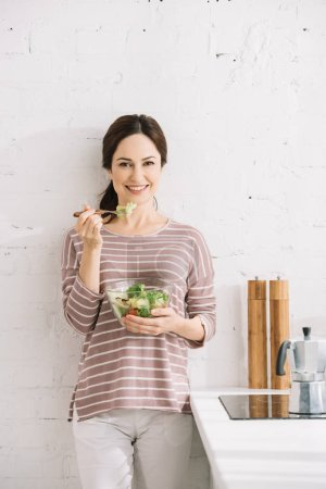 Photo for Young, happy woman looking at camera while standing near wall and eating vegetable salad - Royalty Free Image