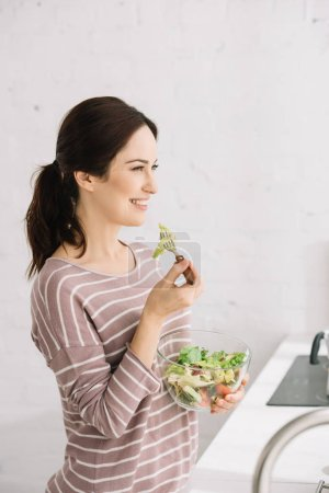 Photo for Attractive, cheerful woman looking away while eating vegetable salad - Royalty Free Image