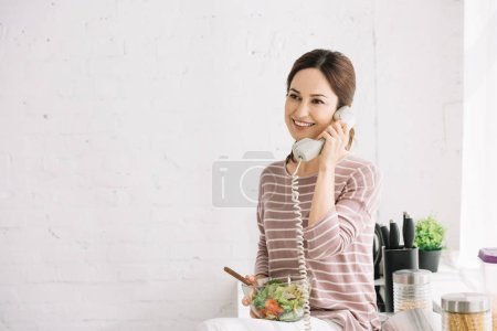 Photo for Smiling woman talking on retro phone while sitting on kitchen table and holding bowl with vegetable salad - Royalty Free Image