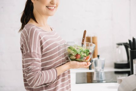 Photo for Cropped view of young, smiling woman holding bowl with vegetable salad - Royalty Free Image