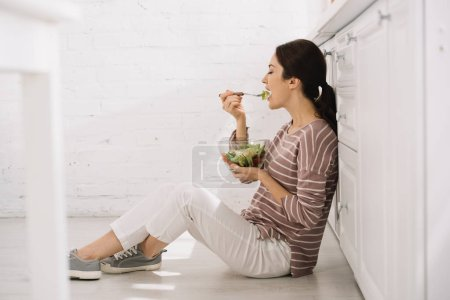 Photo for Pretty young woman sitting on floor in kitchen and eating vegetable salad - Royalty Free Image
