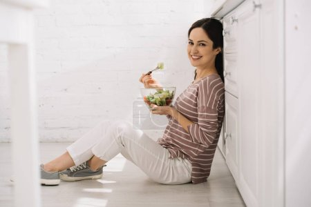 Photo for Selective focus of happy young woman sitting on floor in kitchen and eating vegetable salad - Royalty Free Image