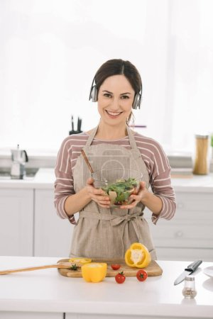 Photo pour Happy young woman in headphones smiling at camera while holding bowl with salad - image libre de droit